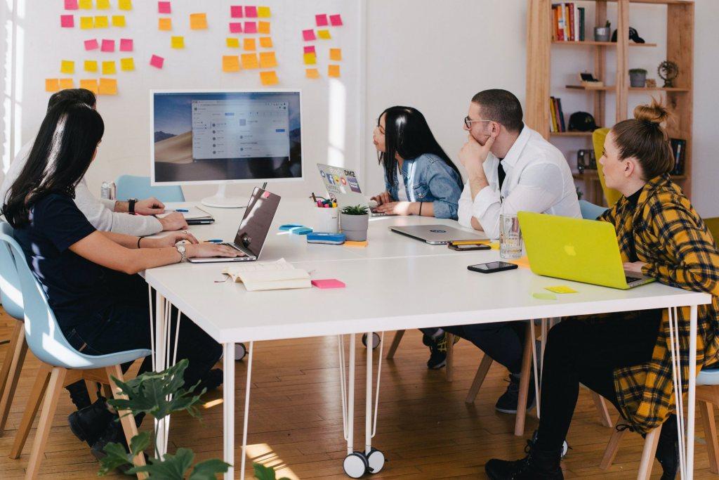 Menschen mit Laptops bei einem Meeting mit vielen Postits an der Wand.