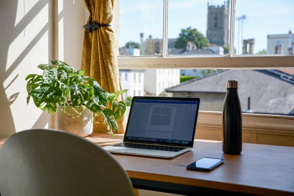 Arbeitsplatz mit Laptop und Blick nach draußen