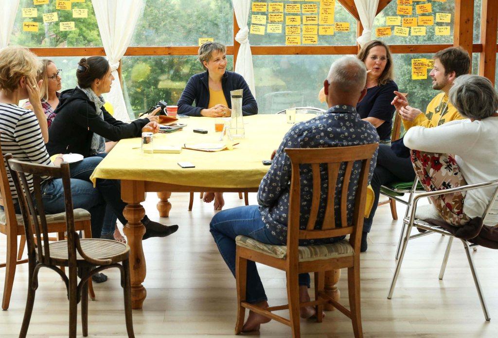 Gruppe von Menschen sitze an einem Tisch und diskutieren